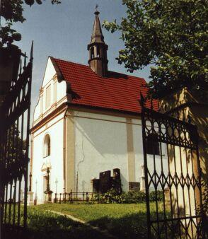 Pohled na kostelík sv. Františka Serafinského z r. 1622 před kovovou hřbitovní bránou.