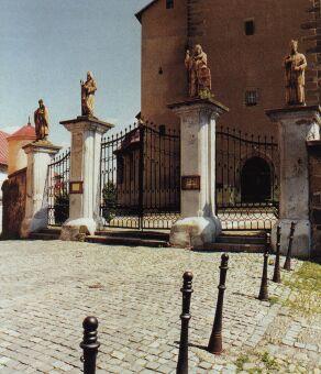 Při vstupu do areálu farního kostela Narození Panny Marie musíme projít kovanou bránou z r. 1809.
