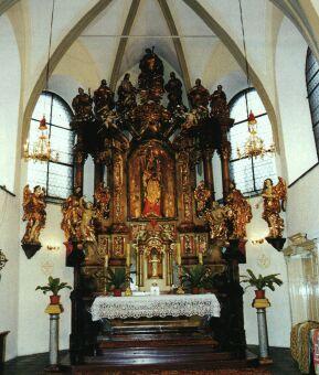 Hlavní oltář farního kostela s gotickou Madonou vyniká pod členitými klenbami.
